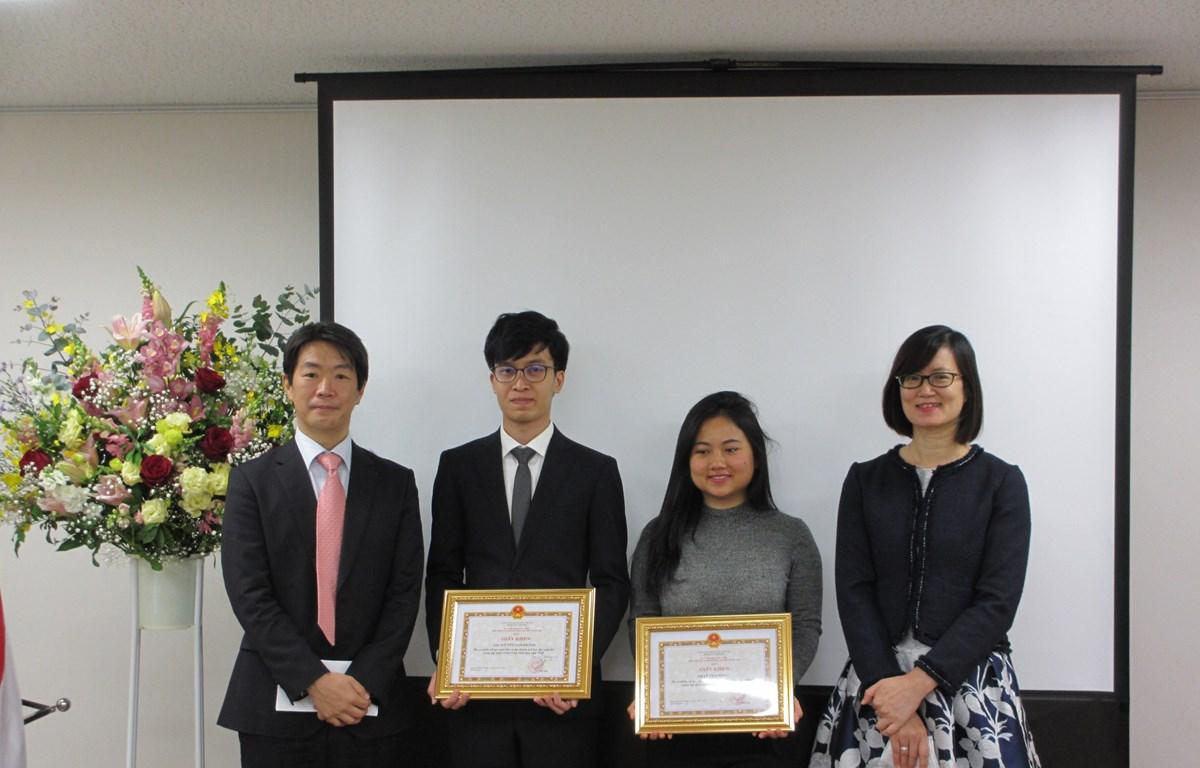 三菱日联金融集团代表Tooru Mera(左一)与越南驻日本大使馆公使林青芳(右一)向越南留学生发放学费津贴。图自越通社
