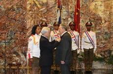 阮富仲总书记向古巴共产党中央委员会第一书记授予金星勋章