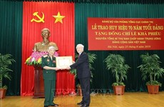 越共中央总书记、国家主席阮富仲向原越共中央总书记黎可漂授予70年党龄纪念章
