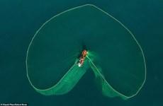 组图:越南渔民在海上抛渔网时撒出的迷人画面