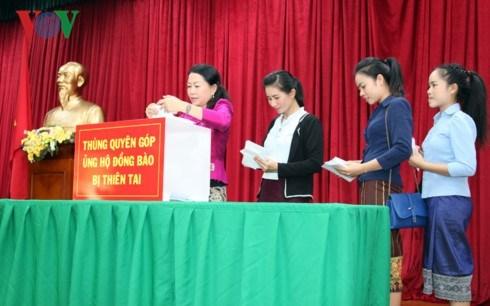 旅居老挝越南人社群为受灾群众捐款 hinh anh 1