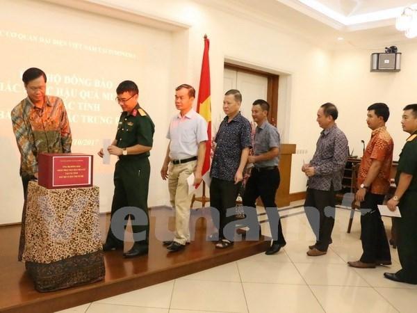 在印尼越南人捐款支持国内受灾群众 协助实现丁有余记者的梦想 hinh anh 1