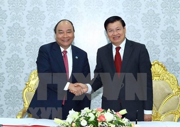 政府总理阮春福和老挝政府总理通伦到老挝星光电信公司参观访问 hinh anh 1