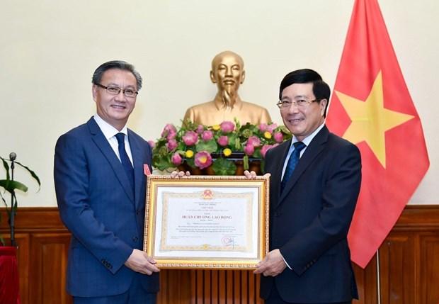 越南政府副总理兼外交部长范平明向老挝驻越大使颁发越南一级劳动勋章 hinh anh 1