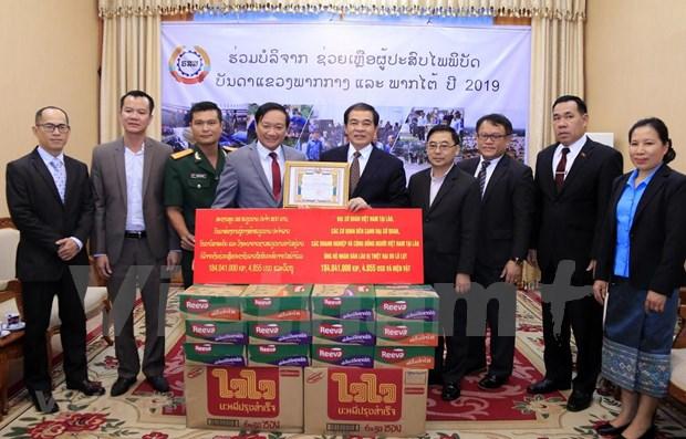 旅居老挝越南人向老挝灾民提供援助 hinh anh 1