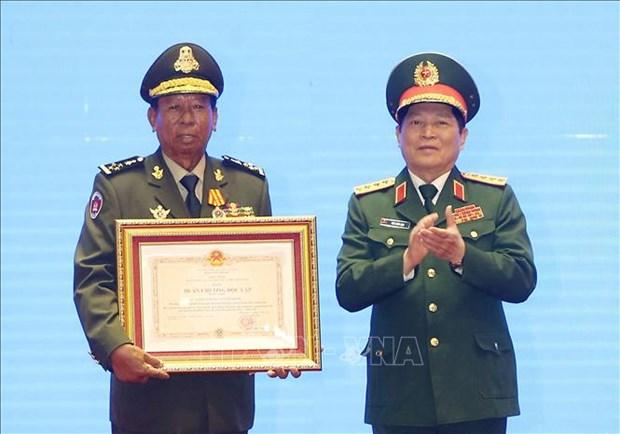 越南、老挝和柬埔寨三国国防部领导和各集体及个人荣获三国的勋章 hinh anh 1