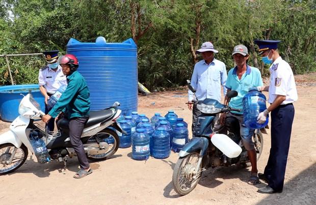 越南海警察司令部向朔庄省干旱和海水入侵灾民捐赠生活用水和医用口罩 hinh anh 2