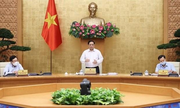 政府总理范明政:恢复和发展经济社会在很大程度上取决于新冠肺炎疫情防控结果 hinh anh 1
